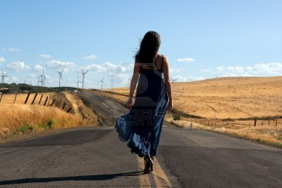 5630653-young-woman-wearing-a-silk-dress-walking-down-a-lonely-road-toward-a-field-of-wind-turbines-searchin